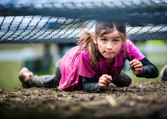 barn kryper på marken i ett hinderbanelopp